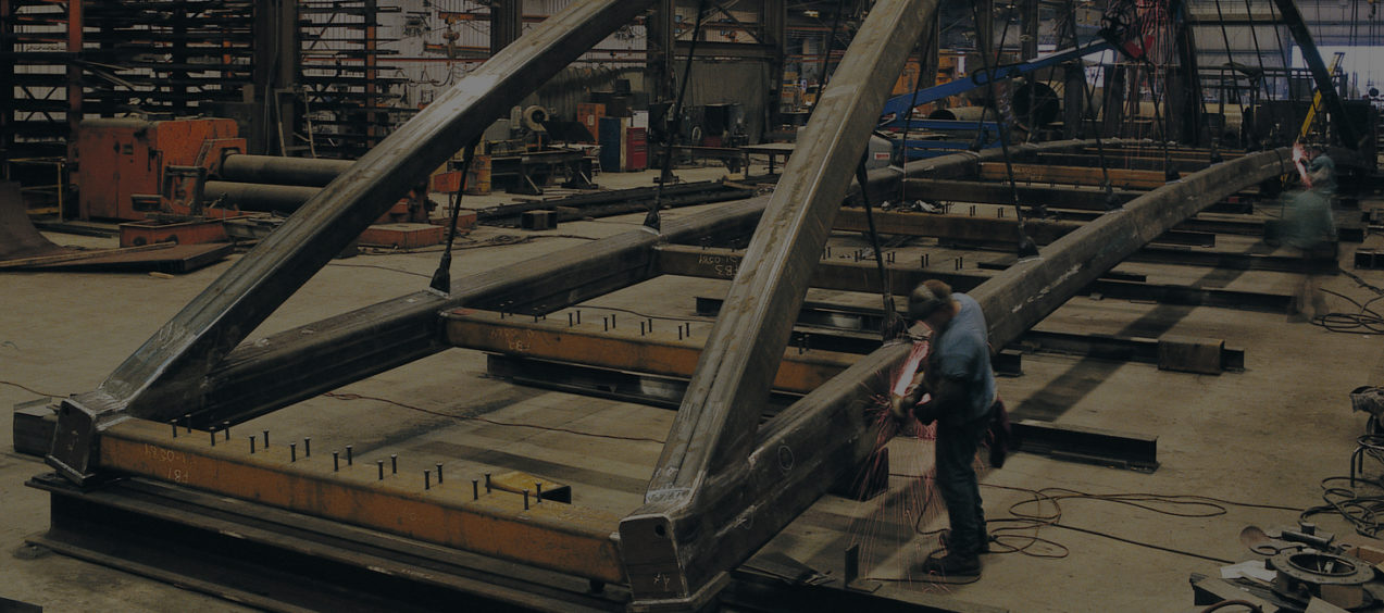 Workers fabricating a steel bridge in a Greiner facility