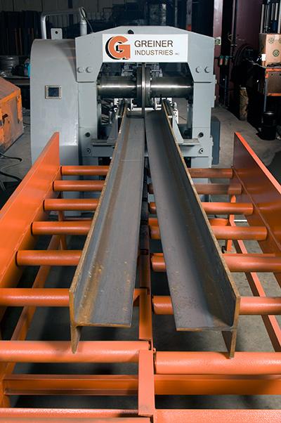 A beam splitting machine shearing a steel i-beam