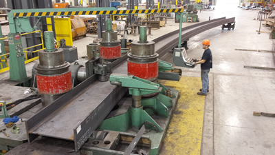 Worker operating a cold cambering machine on an 800 long steel beam at a Greiner facility