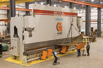 Workers operating Greiner's 2,750-ton press brake at a Greiner facility