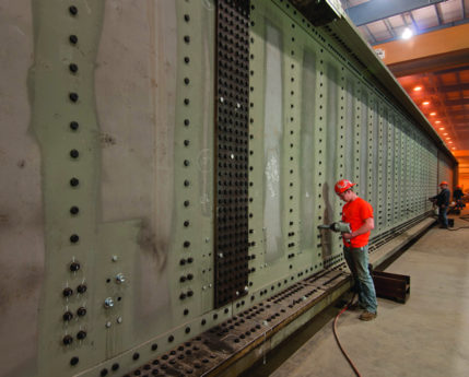 Worker riveting a railroad bridge in a Greiner facility