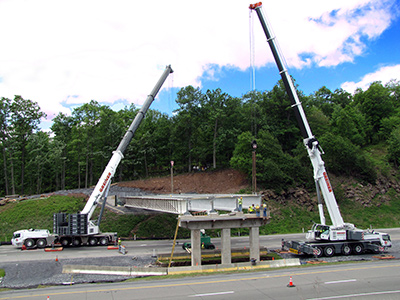 Two mobile cranes installing a bridge over a highway