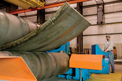 Worker operating Greiner's heavy plate roll machine to roll a steel plate at a Greiner facility