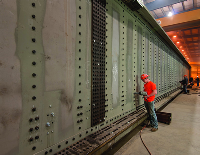 Worker drilling bolt holes in a fabricated railroad bridge at a Greiner facility